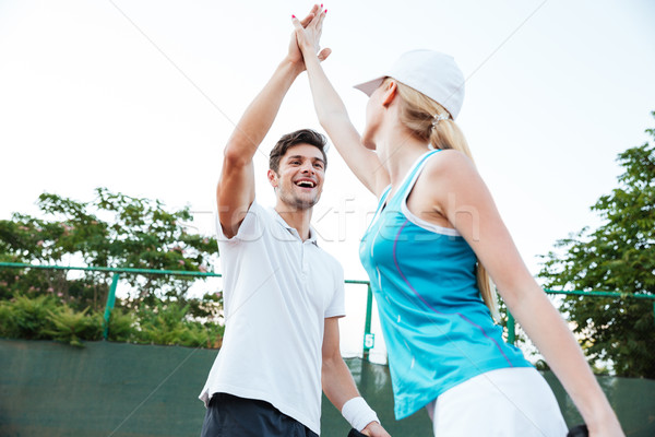 Happy young tennis players Stock photo © deandrobot