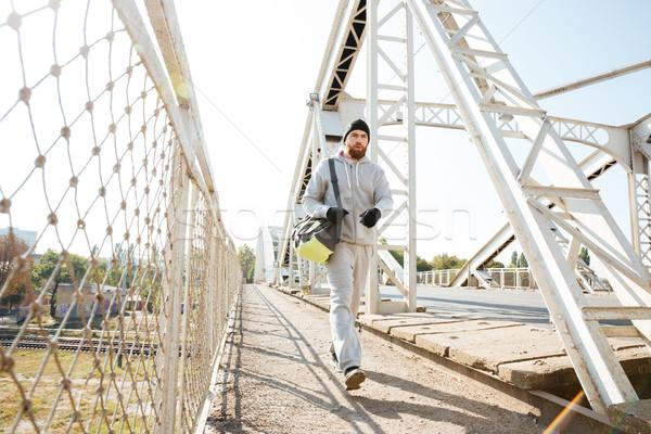 Fiatal szakállas sportok férfi táska sétál Stock fotó © deandrobot