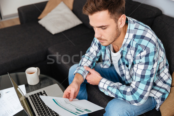 Concentrated young bristle man using laptop and analyzing home finances Stock photo © deandrobot
