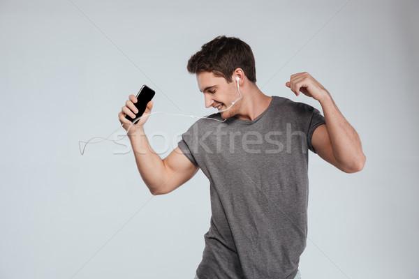 Boldog lezser férfi fülhallgató mobiltelefon tánc Stock fotó © deandrobot
