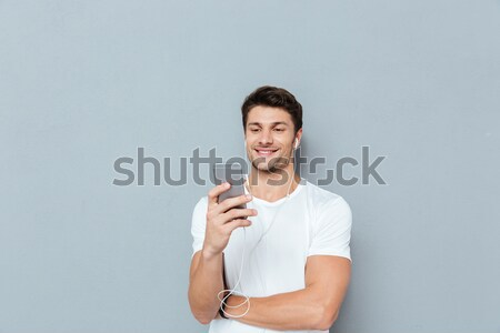 Portrait of a young smiling man pointing finger at condom Stock photo © deandrobot