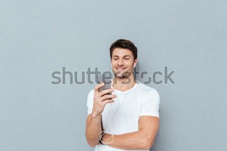 Portré fiatal mosolyog férfi mutat ujj Stock fotó © deandrobot