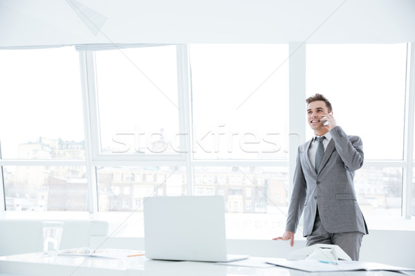 Business man talking at phone near the window Stock photo © deandrobot