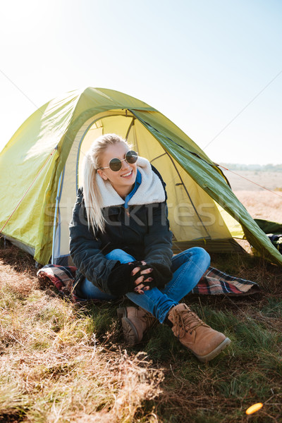 Woman in sunglasses and boots sitting near tent at campsite Stock photo © deandrobot