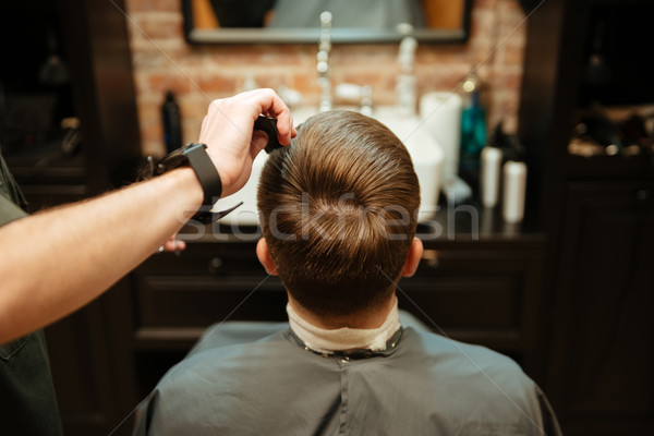 Man getting haircut by hairdresser while sitting in chair Stock photo © deandrobot