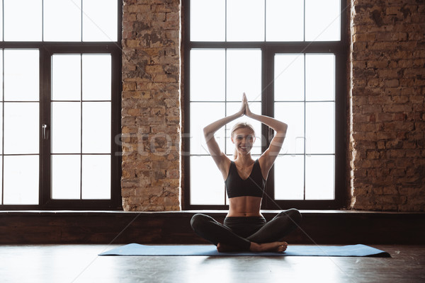 Attractive young fitness woman make yoga exercises. Stock photo © deandrobot