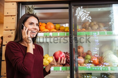 Derűs fiatal nő beszél mobiltelefon választ gránátalma Stock fotó © deandrobot