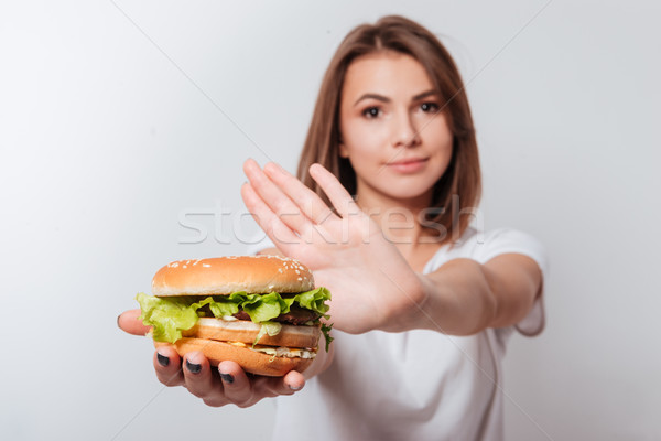 Serious young woman showing fastfood to camera Stock photo © deandrobot