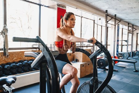 Fitness woman working out on bike in gym Stock photo © deandrobot