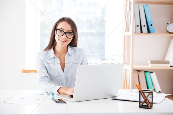 Businesswoman sitting in her office and using laptop Foto stock © deandrobot