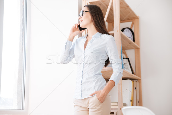 Cheerful businesswoman in her office talking by phone Stock photo © deandrobot