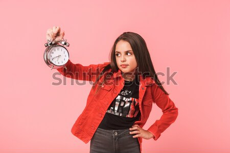 Scared young woman holding alarm clock and looking at camera Stock photo © deandrobot