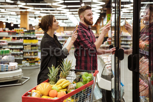 Cheerful loving couple in supermarket with shopping trolley Stock photo © deandrobot