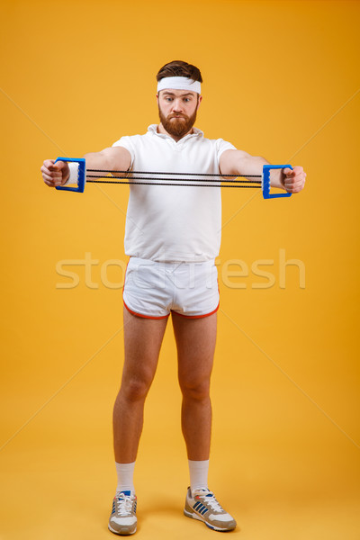 Young athletic man exercising with chest expander or resistance band Stock photo © deandrobot