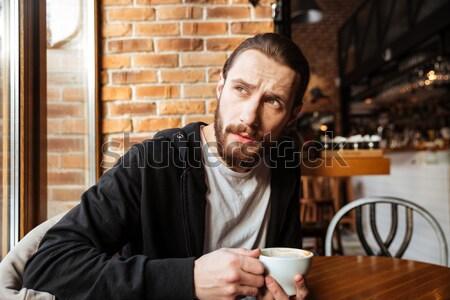 Sorridere barbuto uomo cafe seduta tavola Foto d'archivio © deandrobot