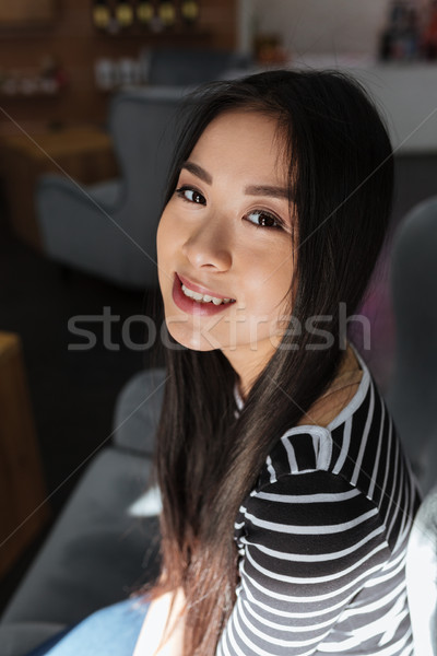 Vertical image of Asian woman sitting in cafeteria Stock photo © deandrobot