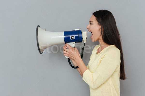 Side view of woman in sweater screaming megaphone Stock photo © deandrobot