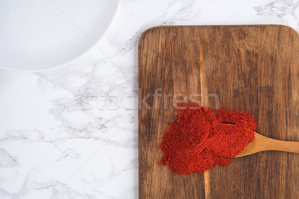 Wooden spoon with paprika powder on a cutting board Stock photo © deandrobot