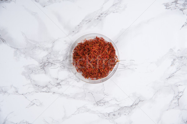 Dried saffron in small bowl isolated on white marble table Stock photo © deandrobot