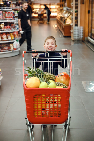 Vertical image of happy boy pushing shopping trolley Stock photo © deandrobot