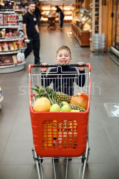 Függőleges kép vidám fiú toló bevásárlókocsi gyümölcsök Stock fotó © deandrobot