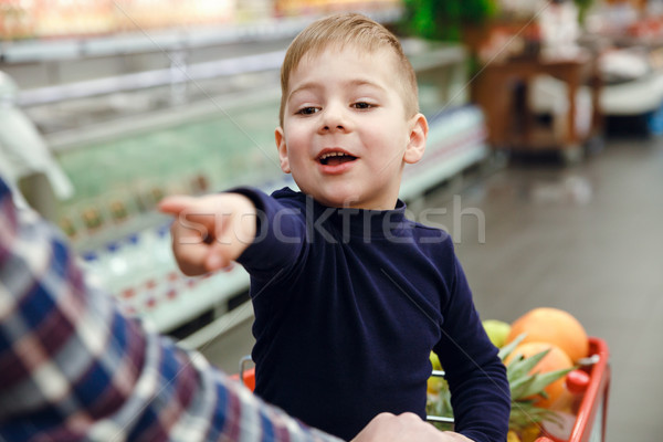 Happy boy sitting on shopping trolley and pointing away Stock photo © deandrobot