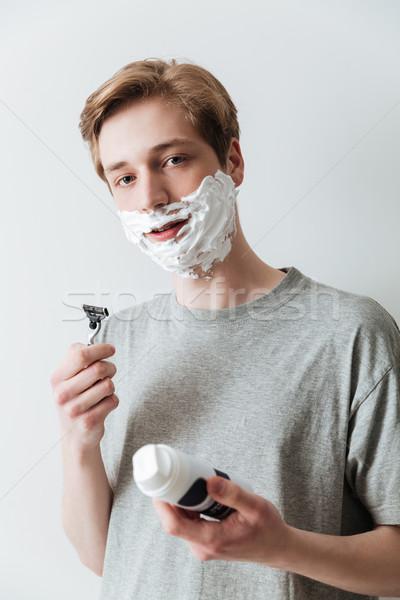 Vertical image of man in shaving foam Stock photo © deandrobot