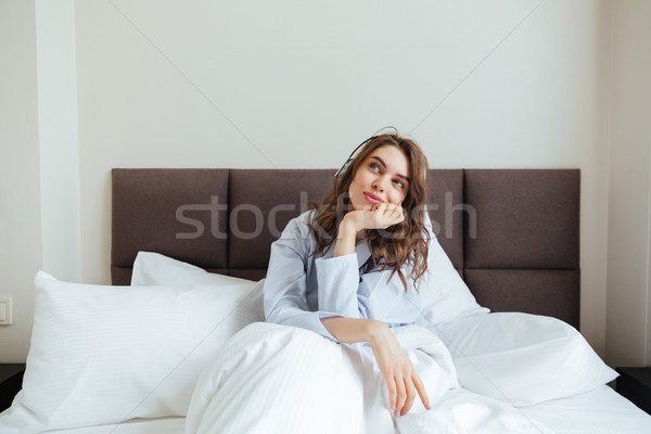 Amazing young lady dressed in pajama lies in bed Stock photo © deandrobot