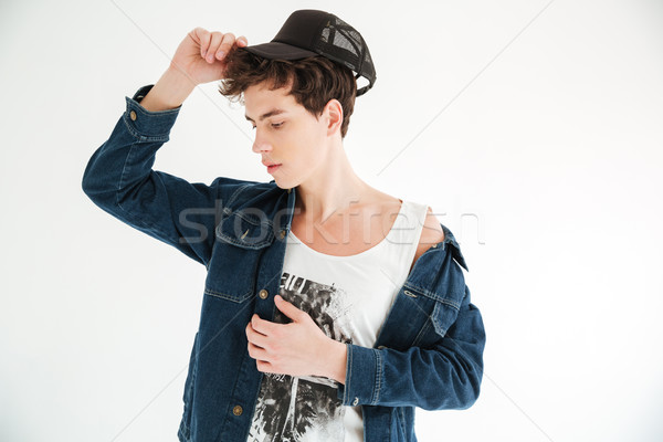 Young mystery man in cap and jeans jacket Stock photo © deandrobot