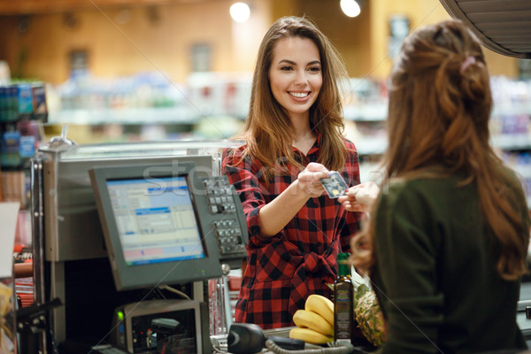 Smiling young lady standing in supermarket holding credit card Stock photo © deandrobot