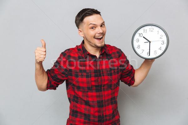 Boldog férfi tart óra mutat hüvelykujj Stock fotó © deandrobot