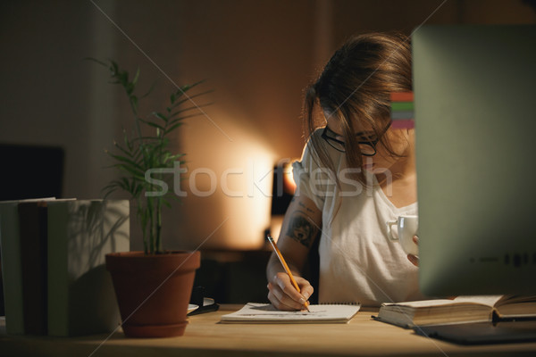 Concentrated young woman designer writing notes using computer Stock photo © deandrobot