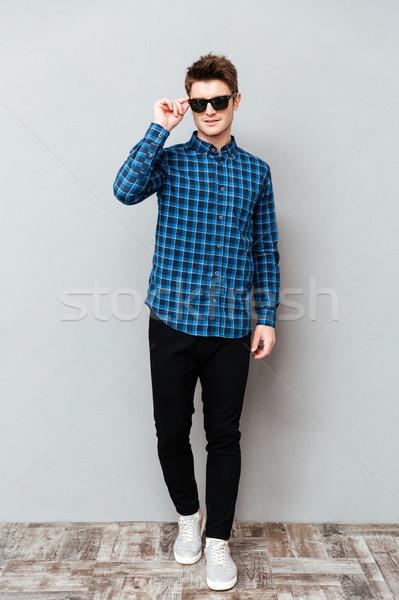 Foto stock: Homem · bonito · óculos · de · sol · em · pé · cinza · parede