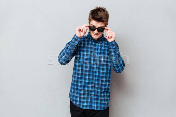 Foto stock: Feliz · homem · óculos · de · sol · em · pé · cinza