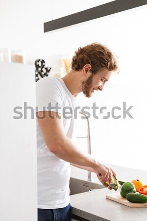 Handsome young sportsman holding glass of juice. Stock photo © deandrobot