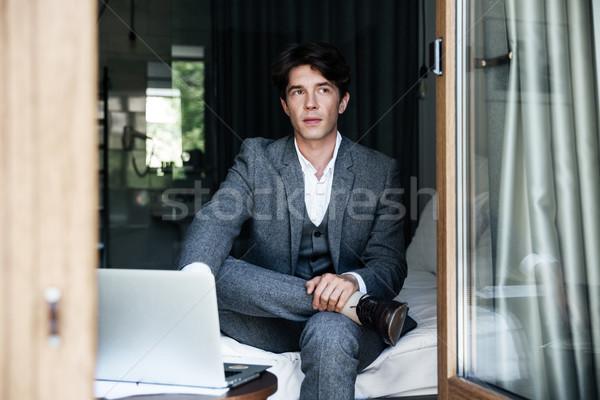 Bem sucedido empresário trabalhando laptop sessão cama Foto stock © deandrobot