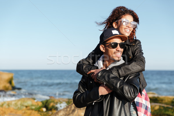 Smiling african loving couple walking outdoors at beach Stock photo © deandrobot