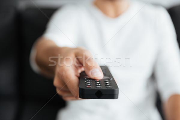 Kép fiatalember tart távirányító ül kanapé Stock fotó © deandrobot