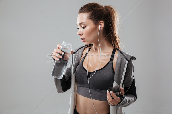 Young sports woman holding bottle of water Stock photo © deandrobot