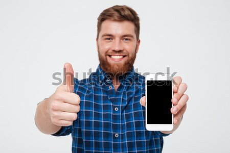 Smiling bearded man showing blank smartphone screen Stock photo © deandrobot