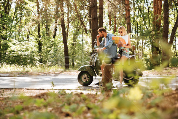 Tired loving couple holding map outdoors sitting on scooter. Stock photo © deandrobot
