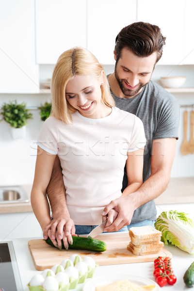 Stock photo: Portrait of happy young couple cooking together in the kitchen