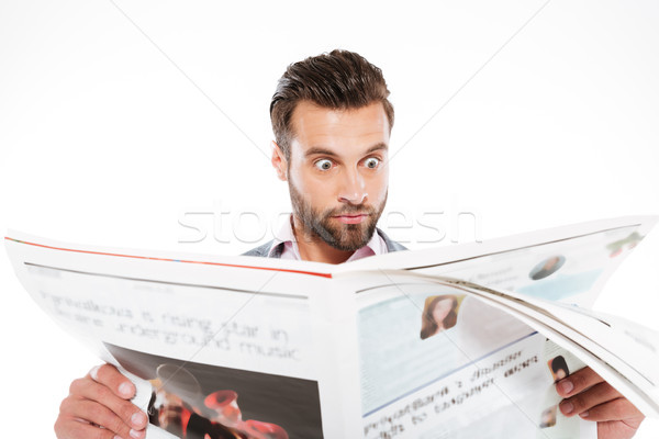Shocked young man reading gazette Stock photo © deandrobot