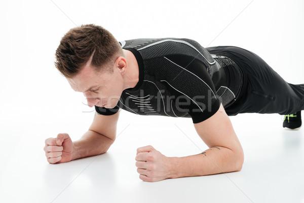 Portré fiatal fitnessz férfi palánk testmozgás Stock fotó © deandrobot