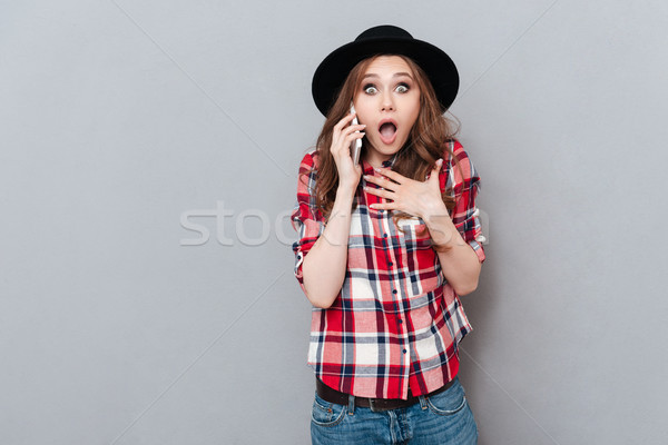 Surprised shocked girl in plaid shirt talking on mobile phone Stock photo © deandrobot