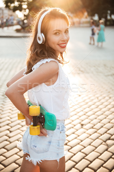 Smiling young woman holding skateboard outdoors Stock photo © deandrobot