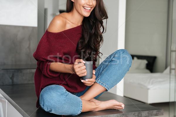 Görüntü kadın oturma mutfak masası gülümseyen kadın fincan Stok fotoğraf © deandrobot