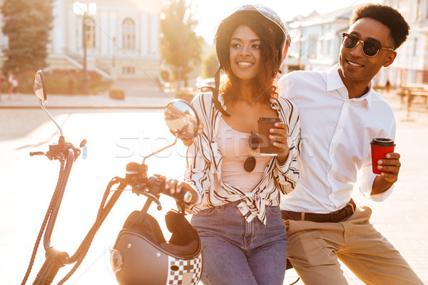 Pleased young african couple drinking coffee while standing near motorbike Stock photo © deandrobot