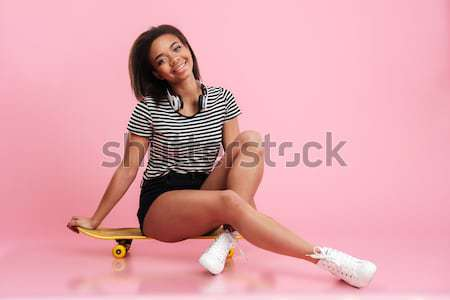 Young smiling woman sitting on skateboard isolated Stock photo © deandrobot