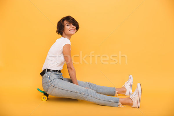 Portrait of a happy excited girl sitting on a skateboard Stock photo © deandrobot